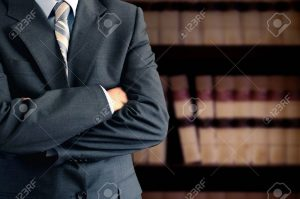 11696462-businessman-wearing-a-suit-in-front-of-a-bookcase