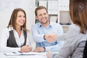26572177-smiling-young-man-shaking-hands-with-an-insurance-agent-or-investment-adviser-as-he-sits-in-a-meetin