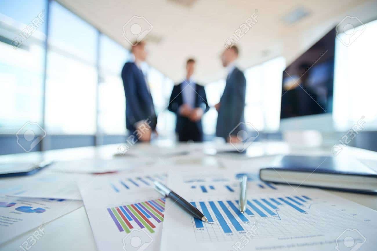 32514135-documents-on-office-table-and-three-men-talking-in-the-background