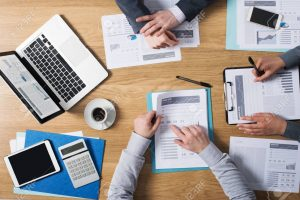 39447129-business-people-team-working-together-at-office-desk-with-laptop-tablet-financial-paperwork-and-repo