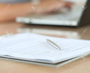44570738-silver-pen-lying-on-document-pad-while-female-hands-working-on-notebook-pc-in-background-