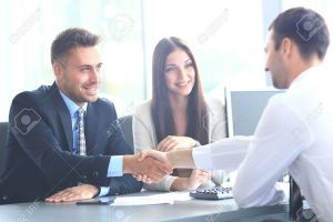 67388055-business-people-shaking-hands-finishing-up-a-meeting