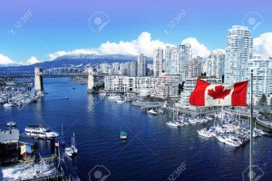 69841834-canadian-flag-in-front-of-view-of-false-creek-and-the-burrard-street-bridge-in-vancouver-canada-