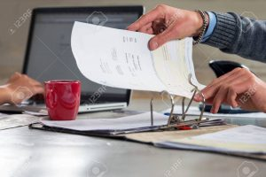 47655918-people-fining-documents-and-doing-their-administration-working-on-a-laptop-and-filing-invoices-and-b