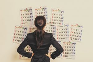 Businesswoman suffering in front of the calendar